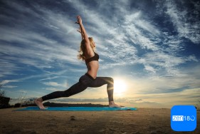 Woman practicing Warrior yoga pose outdoors over sunset sky back